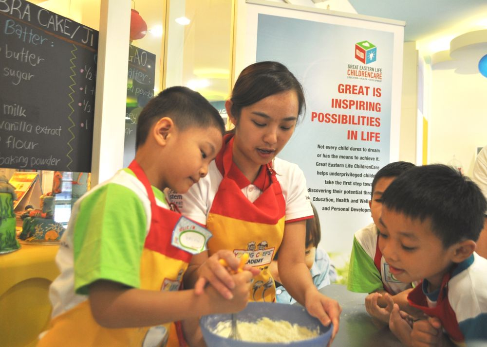 Children mixing their cake ingredients with the help of a Great Eastern Life ChildrenCare volunteer.
